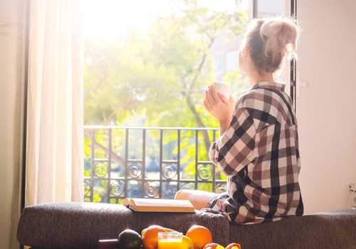 Relaxed woman with hot beverage by open sunny window
