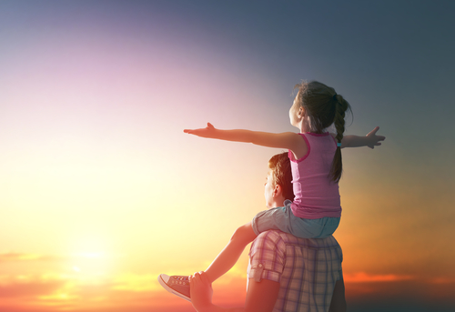 Little girl on shoulders with outspread arms